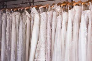 ros of wedding dresses on hangers.