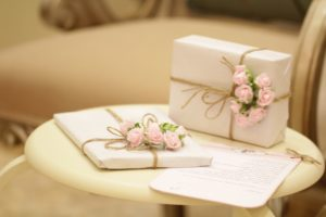 two wrapepd gifts in white on table.