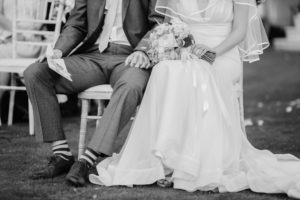 bride and groom holding hands, sitting.