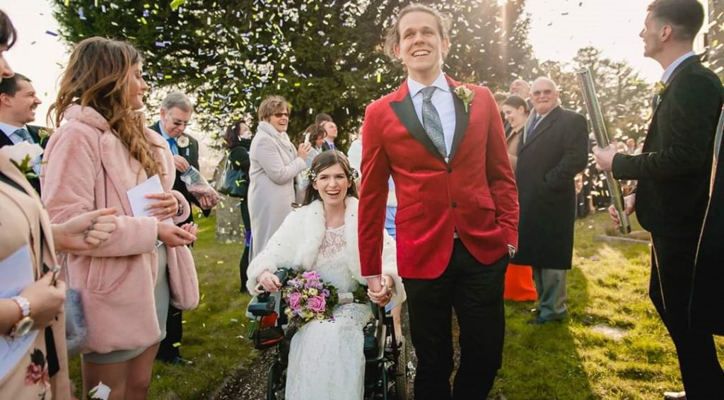 bdire in wheelchair with groom outside.