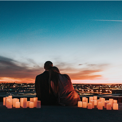 couple watching sunset over city.