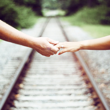 hands holding over train tracks.